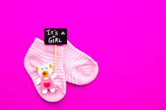 Baby Girl - pink and white socks with bear on pink background with It`s a Girl blackboard sign royalty free stock photos