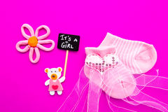 Baby Girl - pink and white socks with bear on pink background with It`s a Girl blackboard sign. Baby Girl announcement - pink and white socks with bear on pink Royalty Free Stock Image