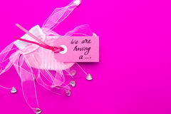 Baby Girl - pink and white socks on pink background with label - we`re having a girl Stock Photos