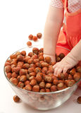The baby girl is plaing with hazelnuts Royalty Free Stock Photo