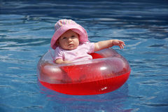 Baby girl in plastic boat. Funny: cute but unhappy baby girl with pink hat, lost at sea in full sun in her red inflatable plastic raft waiting for rescue Royalty Free Stock Image