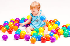 Baby girl play with balls. Baby girl play with lots of colorful  balls, studio shot Royalty Free Stock Photography