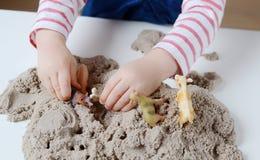 Baby girl play with kinetic sand Stock Photos