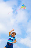 Baby girl play with kite. Adorable baby girl play with colorful kite outdoors, nice kid with toy on blue sky background, spending time in daycare, summer Royalty Free Stock Photos