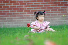 Baby girl play on the lawn, unhappy, miss her mother Royalty Free Stock Photography