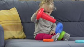 Baby girl play with toy on sofa room. Childhood, education. 4K stock footage
