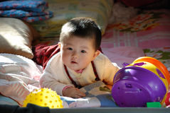 Baby girl playing. Happy baby girl is playing toys on the bed Royalty Free Stock Images
