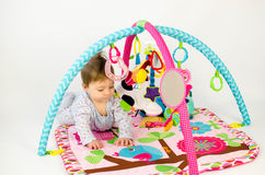 Baby girl playing in an activity gym. Cute baby girl playing in an activity gym Stock Photography