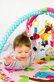 Baby girl playing in an activity gym Royalty Free Stock Photos