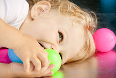 Baby girl playing with balls Stock Photos