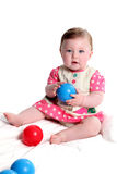 Baby girl playing with balls. Beautiful baby girl playing with red and blue balls royalty free stock photo