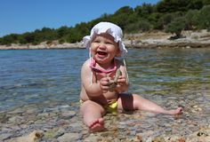 Baby girl playing on the beach Stock Photography
