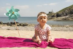 Baby girl playing on the beach. In summer royalty free stock images