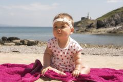 Baby girl playing on the beach. In summer royalty free stock photo