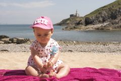 Baby girl playing on the beach. In summer stock images