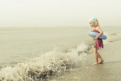 Baby girl playing on the beach. Gorgeous baby girl playing at the seaside Stock Images