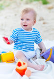 Baby girl playing with beach toys on the beach Stock Images