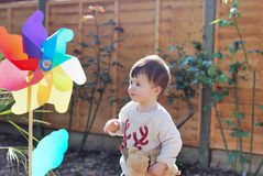 Baby girl playing with a big windmill in the garden Royalty Free Stock Image
