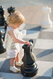 Baby girl playing with chess Royalty Free Stock Photo