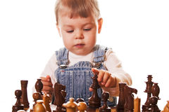 Baby girl playing chess. Baby girl behind chess desk, trying to figure out where to place the chess queen. Isolated on white background stock image
