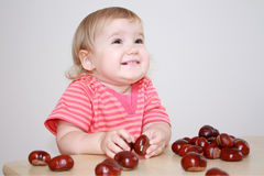 Baby girl playing with chestnuts Royalty Free Stock Image