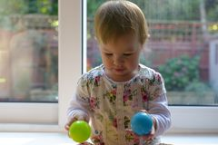 Baby girl playing with colored balls stock photography