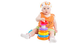 Baby girl playing with colored pyramid build from rings isolated on white background. Toy for children and toddlers to joyfully learn mechanical skills and Royalty Free Stock Photos