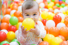 Baby girl playing with colorful balls Royalty Free Stock Photos