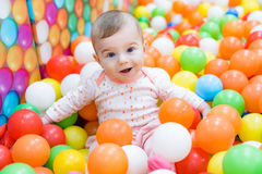 Baby girl playing with colorful balls Royalty Free Stock Photography