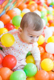 Baby girl playing with colorful balls Stock Images
