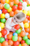Baby girl playing with colorful balls Royalty Free Stock Images
