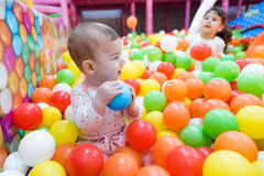 Baby girl playing with colorful balls Stock Photo