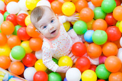 Baby girl playing with colorful balls Stock Photos