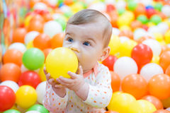 Baby girl playing with colorful balls Royalty Free Stock Image