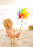 Baby girl playing with colorful windmill toy Royalty Free Stock Photo