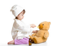 Baby girl playing doctor and giving remedy to toy Stock Photos