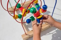 Baby girl playing with educational toy in nursery. Learning colorful wooden toy.developing toy. The labyrinth of wooden stock photography