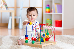 Baby girl playing with educational toy in nursery Stock Photography