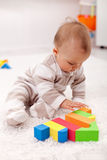 Baby girl playing eith wooden blocks. Sitting on the floor stock photography