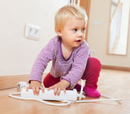 Baby girl playing with electrical extension Royalty Free Stock Photos