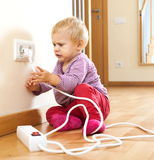 Baby girl playing with electrical extension Royalty Free Stock Photo
