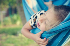 Baby girl playing in the garden in the summer. The girl is sleeping on a hammock. royalty free stock photos