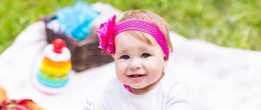 Baby girl playing on the green grass, family picnic close-up Royalty Free Stock Photos
