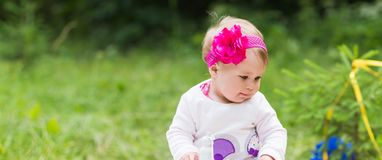 Baby girl playing on the green grass, family picnic close-up royalty free stock photo
