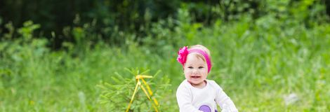 Baby girl playing on the green grass, family picnic close-up royalty free stock photography
