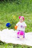 Baby girl playing on the green grass, family picnic close-up stock images
