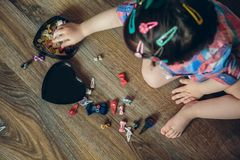 Baby girl playing with hair clips sitting in the floor Stock Images