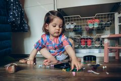 Baby girl playing with hair clips sitting in the floor Royalty Free Stock Photo