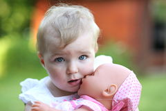 Baby girl playing with her doll Stock Photos