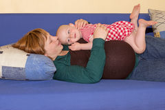 Baby girl playing with her pregnant mother Stock Photos